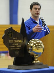 Joe Birkhauser stands next to one of the girls basketball