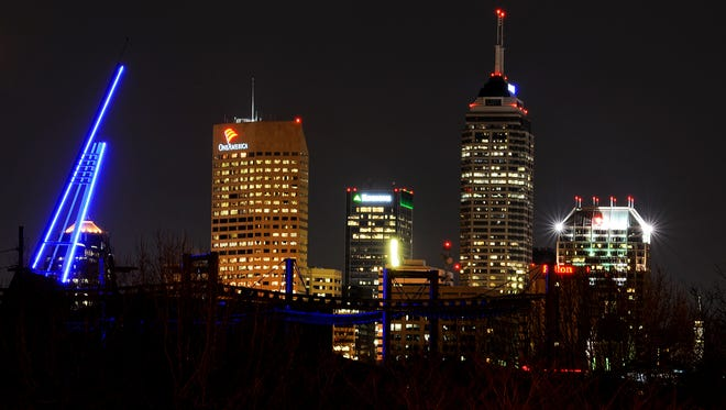 The Indianapolis skyline is seen behind the Beacon of Hope, left, that was lit by the Indianapolis Zoo, Thursday, March 13, 2014.