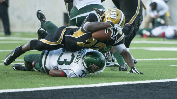 Alabama State running back Malcolm Cyrus scores over Mississippi Valley State Mark Pegues on Saturday. Alabama State running back Malcolm Cyrus (22) scores over Mississippi Valley State Mark Pegues (33) during the game between Alabama State and Mississippi Valley State on Sept. 13, 2014, at The New Hornet Stadium in Montgomery, Ala.