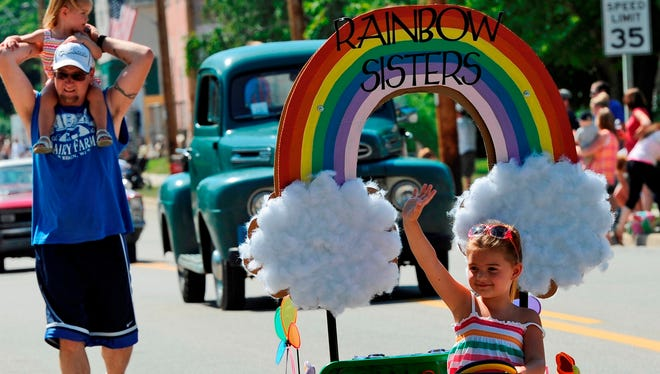 Karlee Tavs, 5, drives her own float in the Van Dyne parade to celebrate small town U.S.A. in 2013. Her dad, Scott, and her little sister, Ana, 2, follow behind her handing out freeze pops.