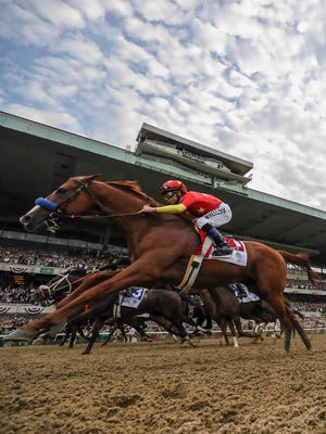 Justify and jockey Mike Smith pass the grandstands for the first time on their way to winning the Belmont Stakes and the Triple Crown. June 9, 2018