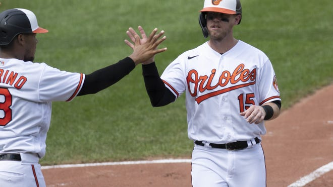 Baltimore Orioles' Chance Sisco high fives Pedro Severino after scoring during the third inning of a baseball game against the Boston Red Sox on Sunday in Baltimore.