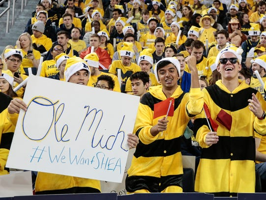 A Michigan fan holds a sign of #WeWantSHEA, referring