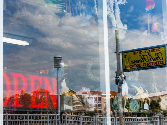 A sign for Kelly's Fish House is reflected in the window