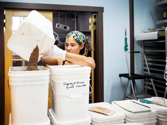 "Sara Castillo, head chocolatier at French Broad Chocolates, pours chopped chocolate into a bucket to be used in pastries in the Chocolate Lounge or, Castillo said, ""in anything from ice cream to cakes."""