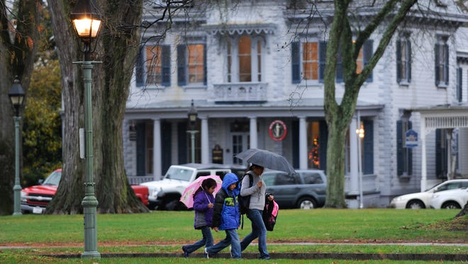 People walk through the rain on South State Street on the Green in Dover Thursday afternoon.