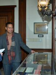 Mario González, executive director of the Passaic Public Library, shows off some of the items and documents on display.