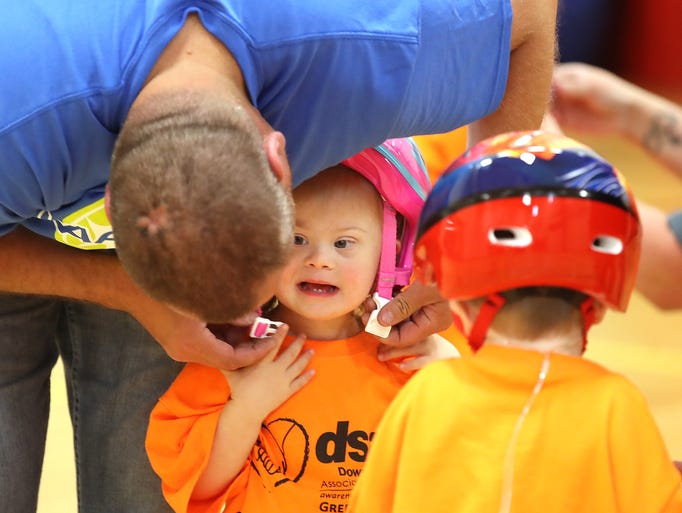 Anna gets help with her helmet strap from volunteer