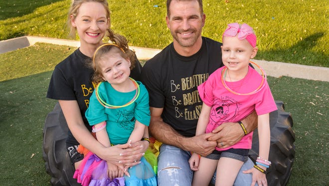 Sherri and Jerrod Goering and their daughters, Adelle and Ella, take a break at the fundraising run for Ella, who has been diagnosed with a brain tumor.