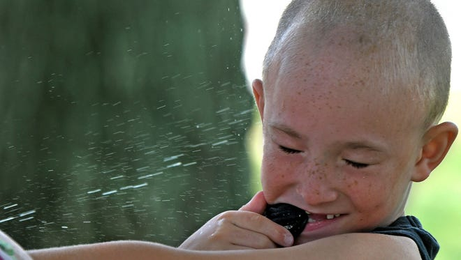 Rickie Brooks, age 6 of Mansfield, gets some relief from the heat Wednesday afternoon in Central Park with the help of a squirt gun.