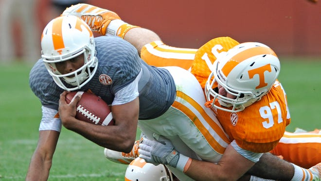 Tennessee quarterback Jauan Jennings, left, is tackled by defensive lineman Zac Wright (97) and defensive back Evan Berry (29) during the Orange and White game Saturday at Neyland Stadium.