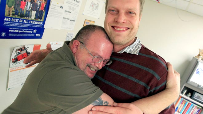 Former resident Todd Gorrell grabs Client Services Coordinator Chris Lashock in a spontaneous embrace while visting Homeless Connections earlier this month.