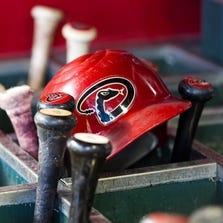 Diamondbacks bats and a helmet sit int he dugout at Chase Field in Phoenix.