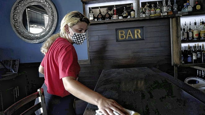 Summer Spaun cleans and disinfects the bar at Revelry Tavern, 6711 Dublin Center Drive, on July 8. The COVID-19 coronavirus pandemic has restaurants exploring new business models and practices for everything -- from cleaning to online ordering and delivery methods.