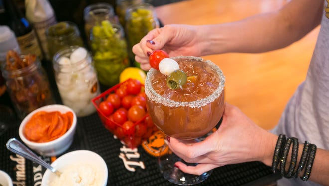 Bartender Laura McCarthy places condiments on a Bloody Mary at the Arcadia Tavern in Phoenix as seen on Saturday, December 13, 2014.