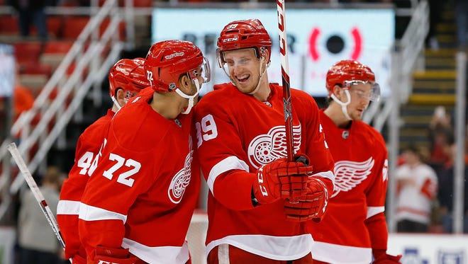Detroit Red Wings right wing Anthony Mantha (39) laughs with Andreas Athanasiou (72) after beating the Montreal Canadiens on March 24, 2016, in Detroit.