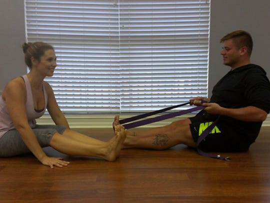 Chiodo and Simmons   demonstrate seated forward bend. Note the bend in the knees.