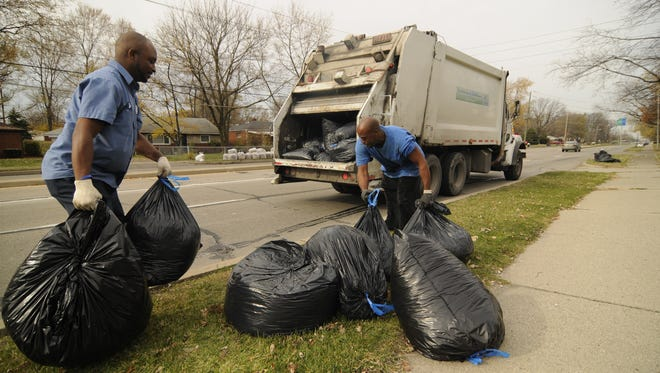 Emmit Townsend, left, and Ronald Harper throw bags onto the DWP truck driven by Kia Bible at 39th and Arlington.