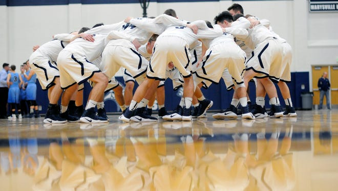 The Vikings huddle together before the game Monday, Mar. 6, during boys district basketball action at Marysville High School.