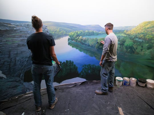 Brothers Aaron (left) and Adam Wolken paint a mural of the White River at Wonders of Wildlife National Museum and Aquarium on Tuesday, Sept. 12, 2017. The two brothers have spent years bringing scenes to life in exhibits all over the museum and aquarium.