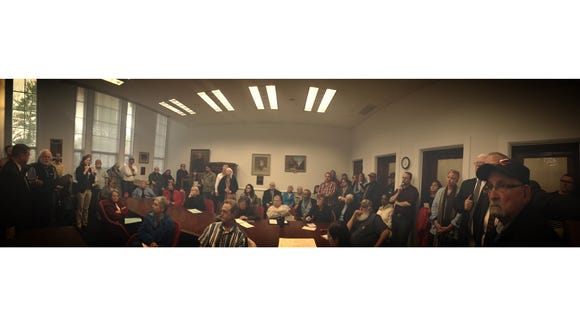 A large group crowds into a tiny room at the Staunton