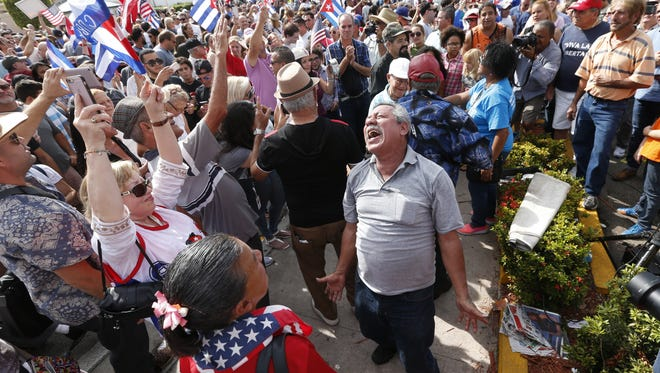 AP Members of the Cuban community react to the death of Fidel Castro on Saturday, Nov. 26 in the Little Havana area in Miami. Members of the Cuban community react to the death of Fidel Castro, Saturday, Nov. 26, 2016, in the Little Havana area in Miami. Castro, who led a rebel army to improbable victory in Cuba, embraced Soviet-style communism and defied the power of 10 U.S. presidents during his half century rule, died at age 90. (AP Photo/Wilfredo Lee)
