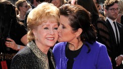 Carrie Fisher kisses her mother, Debbie Reynolds in