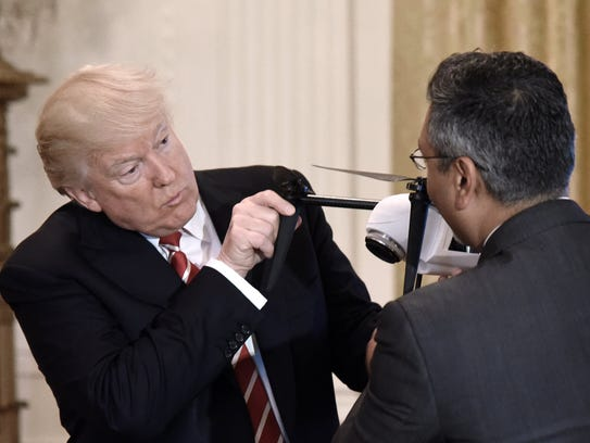 President Trump holds a drone as George Mathew, CEO