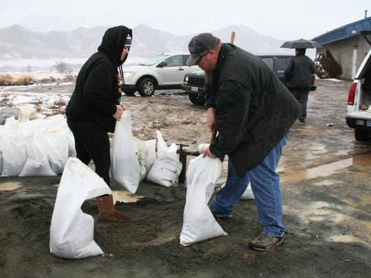 Dayton residents and volunteers gather up sandbags in January in preparation for flooding at the Central Lyon County Fire Protection Distriction Station 39.