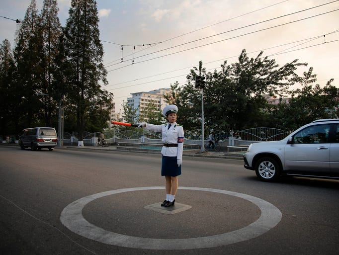 A North Korean traffic police woman directs vehicles