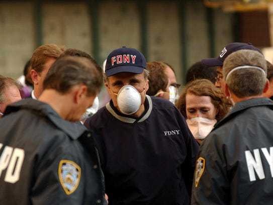 New York Mayor Giuliani wears a dust mask after a tour