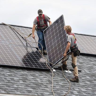 Installing solar panels on a house in Shelburne, Vt.,