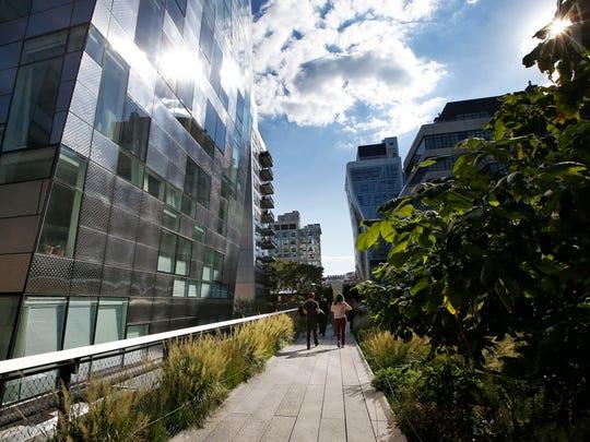 Pedestrians stroll between luxury apartment buildings