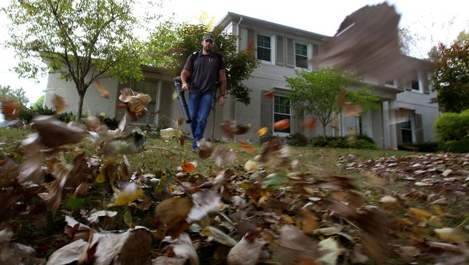 Stars and Stripes Lawn Care co-owner Chris Kamyszek uses a leaf blower to clean up a client's yard in Bloomfield Hills, Mich., on Friday, Oct. 9 2015. Kamyszek thinks that the use of an app like the one from Plowz & Mowz, will help shape the industry.
