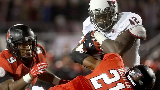 Ball State's Martez Hester brings Northern Illinois' Cameron Stingily down as Michael Ayers comes to help.