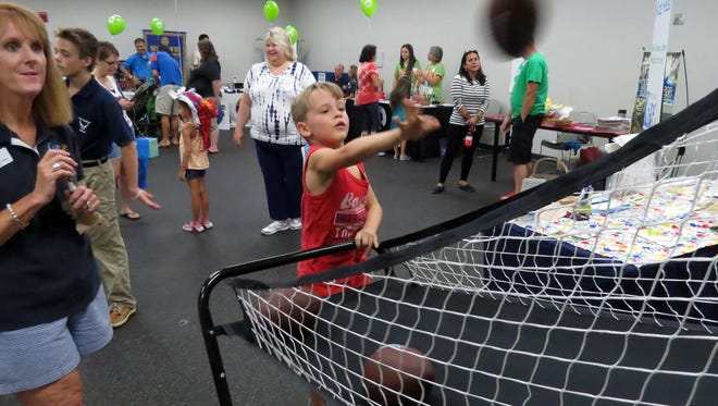 Blane McGuire, 7, tries his luck at the football toss, a attraction put on by the Santa Rosa Kid's House for the entertainment of children attending the Gulf Breeze Business & Family Expo Saturday at the Gulf Breeze Community Center.