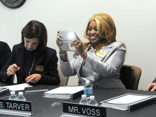 Commissioner Linda Lee Tarver records the moment as Michigan Governor Rick Snyder  enters to speak at a meeting of the Michigan Civil Rights Commission in downtown Lansing Monday  Jan. 26,  2015.