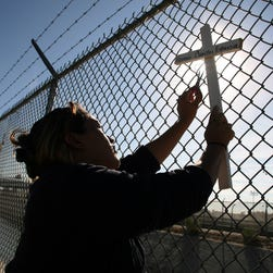 Abigail Arredondo of the Border Network for Human Rights works to remove a memorial cross from the fence which runs along the U.S.-Mexico border Wednesday Nov. 5, 2008 in El Paso, Texas. She and companions were taking down the crosses which had been placed on the fence last week as part of a Day of the Dead (Nov. 1) tribute for migrants who have died crossing the border.