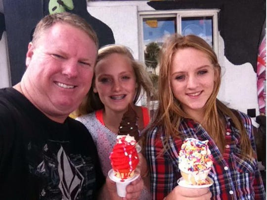 Michael Higgins, a little over 100 pounds ago, enjoying a frozen treat with his daughters Lacey and Riley.