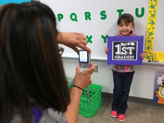 Purple Heart Elementary School first grader Mayte Miranda had a picture taken by teacher Cynthia Castillo Tuesday at the Socorro Independent School District's newest elementary school.