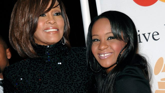 In this Feb. 12, 2011, file photo, singer Whitney Houston, left, and daughter Bobbi Kristina Brown arrive at an event in Beverly Hills, Calif.  The daughter of late singer and entertainer Whitney Houston was found Saturday, Jan. 31, 2015, unresponsive in a bathtub by her husband and a friend and taken to an Atlanta-area hospital. The incident remains under investigation.