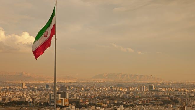 An Iranian flag waving in the wind above the skyline of Tehran.
