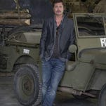 "Brad Pitt leans on a jeep for the film ""Fury,"" at the Tank Museum in Dorset, southern England. He went to work Thursday wearing his wedding ring for the first time."