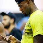 LeBron James looks at his cellphone during the LeBron James Skills Academy on Thursday in Las Vegas.