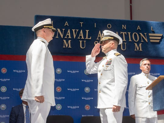 Incoming Center for Information Warfare Training Commanding Officer Capt. Nicholas Andrews II, right, salutes outgoing Commanding Officer Capt. Bill Litz during the Change of Command ceremony at the National Naval Aviation Museum in Pensacola on Thursday, May 24, 2018.