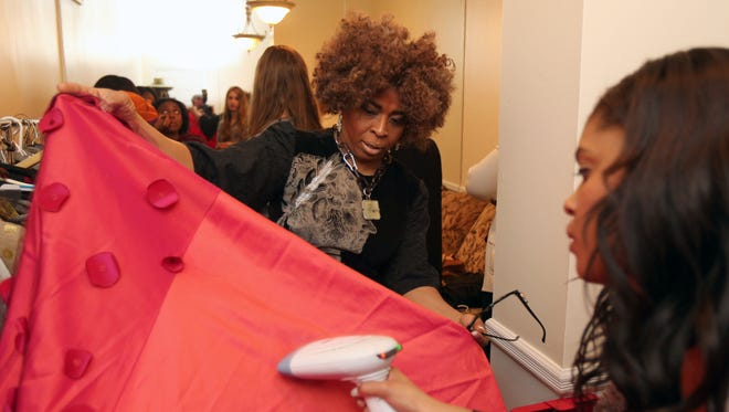 Hope Wade, a fashion designer from Pomona, has the wrinkles steamed out of a dress that is part of her collection during a fashion show at the Ageno Foundation International Inc. fundraiser at The Riverview in Hastings-on-Hudson.