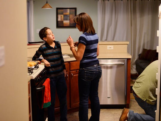 Tima Good, center, gets ready for dinner with her son, 10-year-old Eric Good. Though she's celebrated Thanksgiving every year, this will be her first as an American. A native of France, she became a U.S. citizen earlier this year.