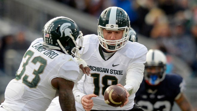 Michigan State quarterback Connor Cook hands the ball to Jeremy Langford during the first half of an NCAA college football game against Penn Statae in State College, Pa., Saturday, Nov. 29, 2014.