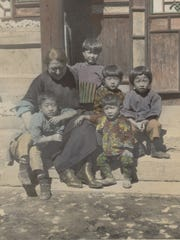 Archive photograph taken in the early 20th century of Church of the Brethren missionary Nettie M. Senger sitting on the steps with children in China.