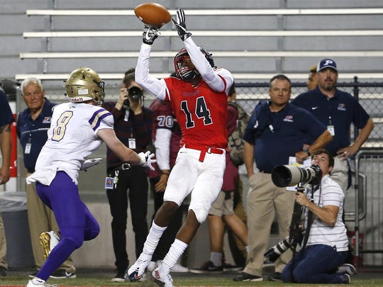 Centennial Dyelan Miller (14) scores a touchdown while being defended by Notre Dame Prep Quinn Stanton (8) during the 5A high school football state championship game at Arizona Stadium in Tucson on December 1, 2017.